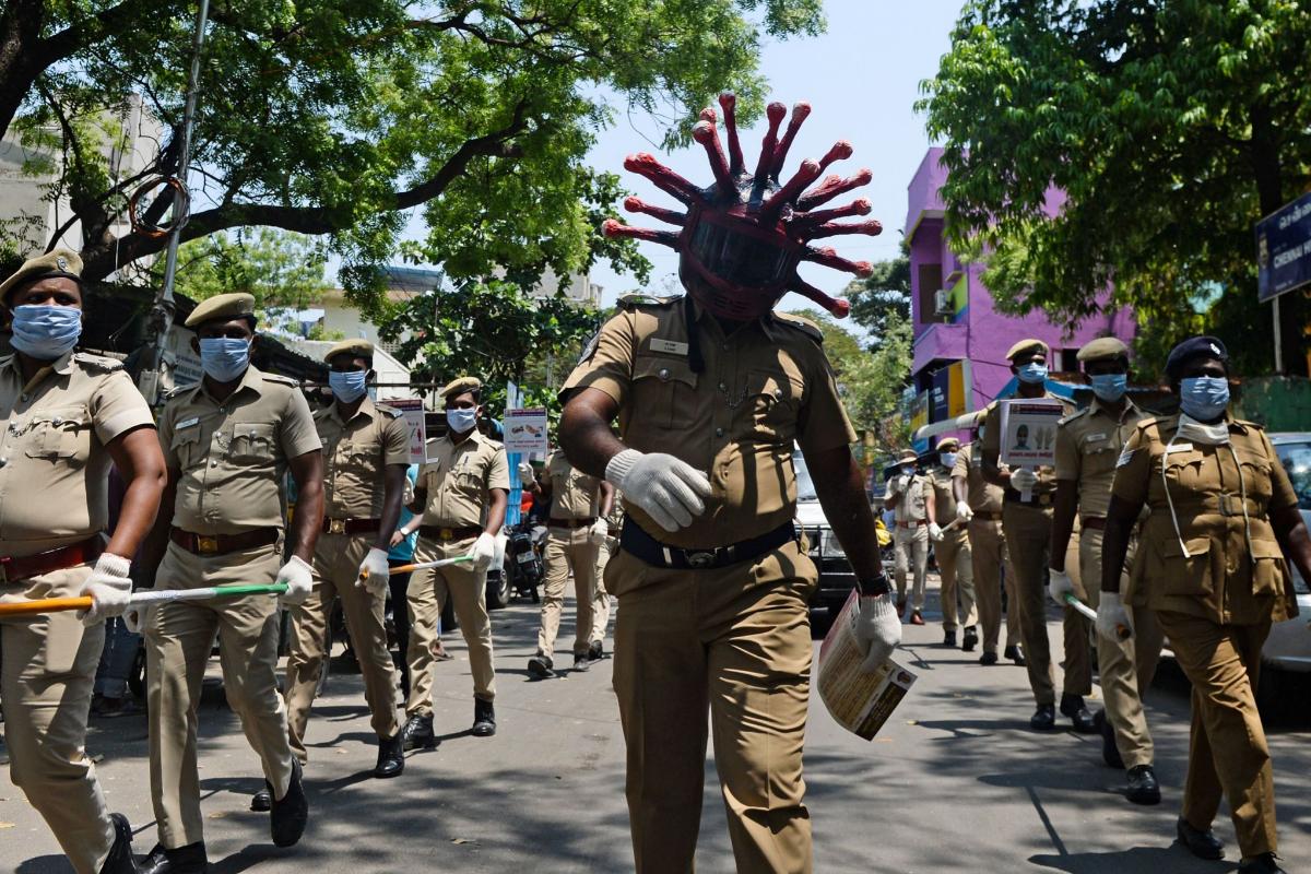 Un policía con un casco que representa al coronavirus, durante una marcha junto a otros policías para concienciar sobre el coronavirus en Chennai, India.