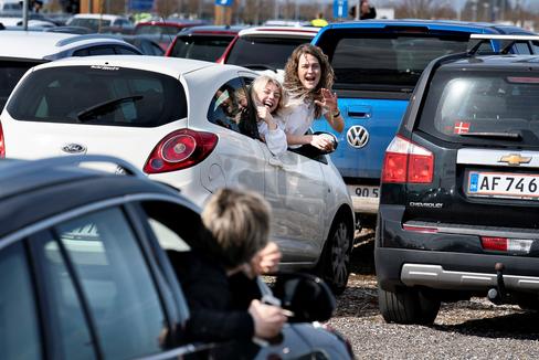 Unos jóvenes se saludan entre coches en un atasco camino del aeropuerto de Aarhus en plena pandemia.