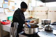 Una inmigrante cocina en un albergue, en Valladolid.