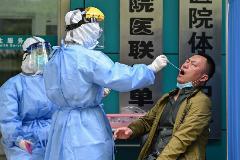 Dos trabajadores médicos realizan un test de Covid-19 a un hombre en Wuhan.