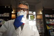 Farmacéutico en una farmacia con mascarilla por el coronavirus