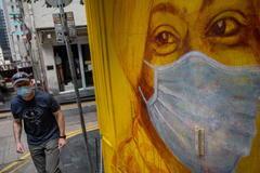 Un hombre pasa frente a un mural en Hong Kong.