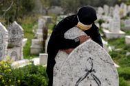Una mujer siria sobre la lápida de un pariente.