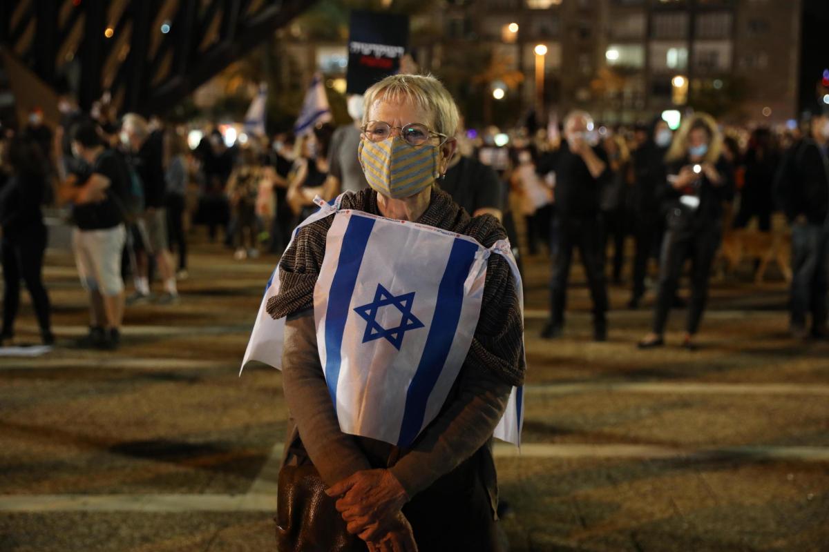 Uno de los manifestantes ataviado con mascarillas y la bandera de Israel. | EFE