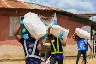Volunteers carry sacks filled with food to distribute to vulnerable residents, during a lockdown by the authories in efforts to limit the spread of the coronavirus disease (COVID-19), in Lagos