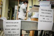 La trabajadora de una farmacia selecciona mascarillas para luego entregar a uno de los usuarios que las pida