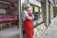 Una trabajadora a las puertas de su negocio en Getxo, durante la crisis del coronavirus.