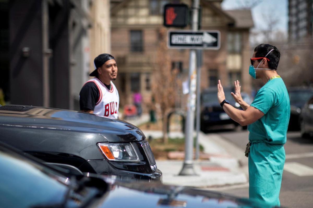 Un médico impide el paso a un manifestante en Denver.