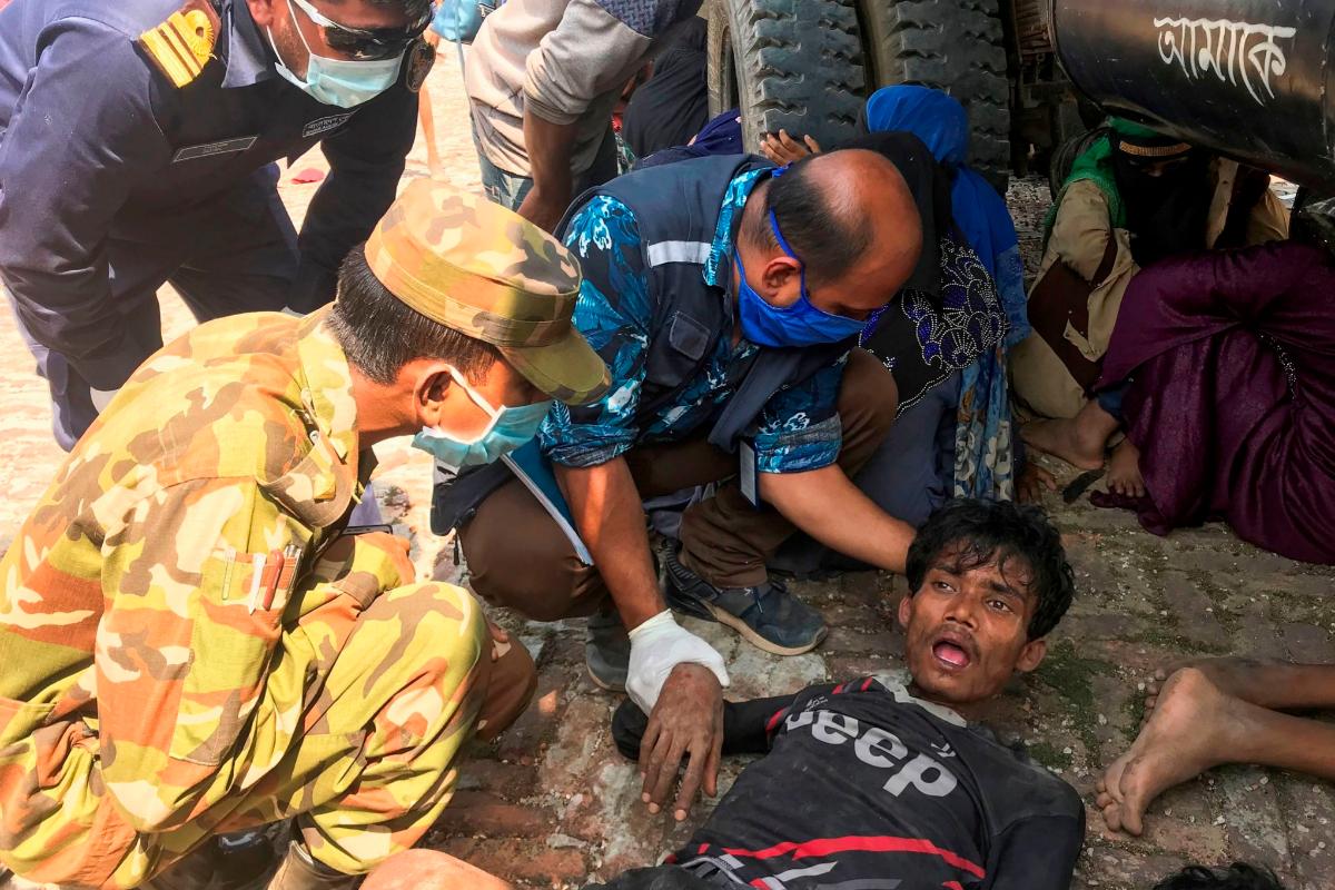 Personal de seguridad de Bangladesh atiende a un refugiado rohingya en Teknaf.
