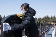 Una mujer limpia una lápida en uno de los cementerios de Harbin (China)