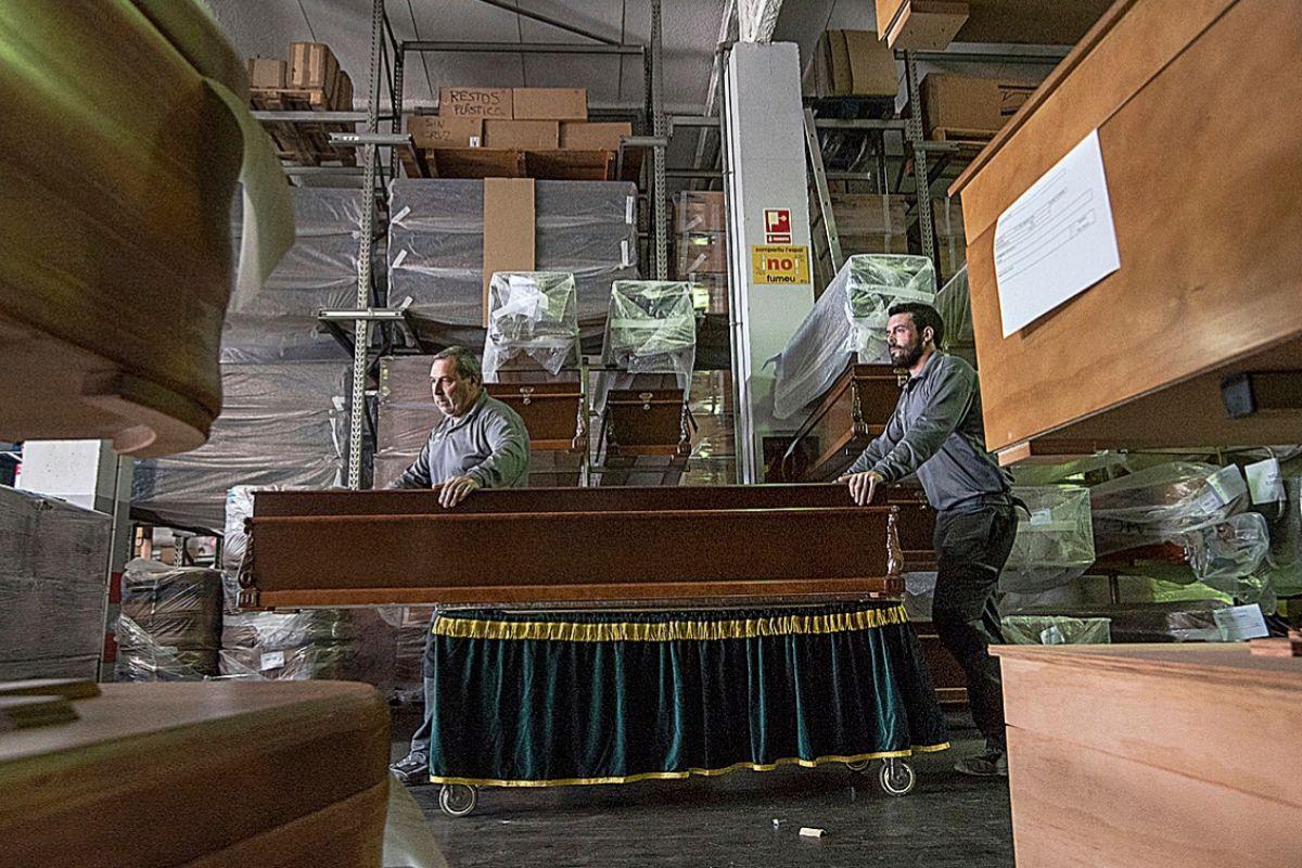 Dos enterradores empujan un ataúd en uno de los almacenes de la Empresa Funeraria Municipal de Palma donde trabajan 93 empleados.