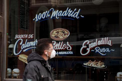 Un hombre pasa junto a un restaurante del centro de Madrid, cerrado por el estado de alarma