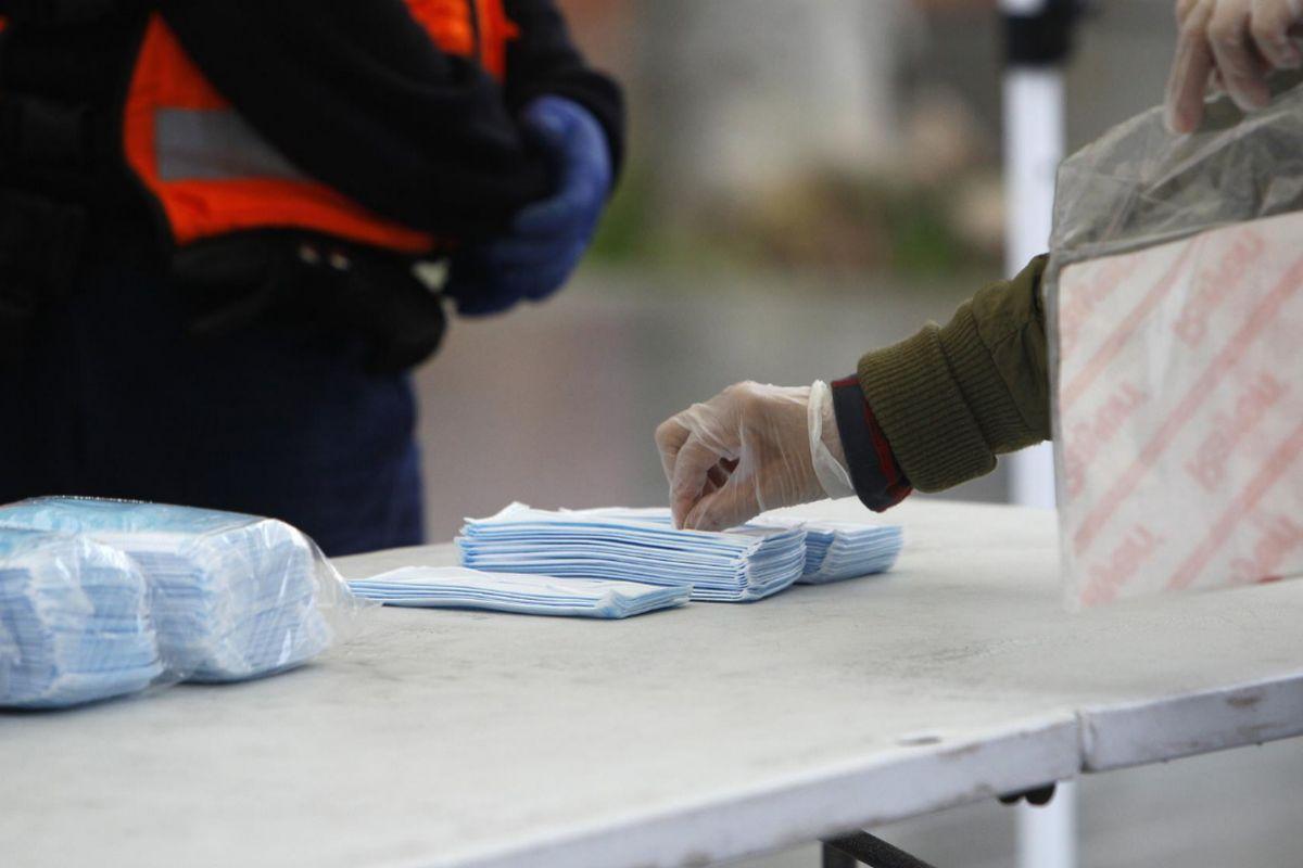 Transeúntes recogen mascarillas para viajeros y usuarios de transporte público en las inmediaciones de la estación Intermodal de Palma
