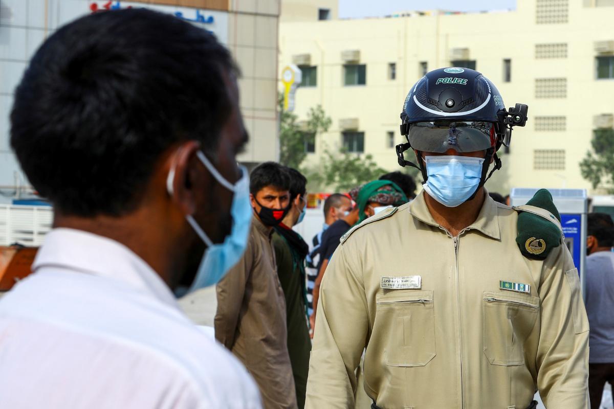 Un agente di polizia controlla la temperatura di un lavoratore venerdì a Dubai.