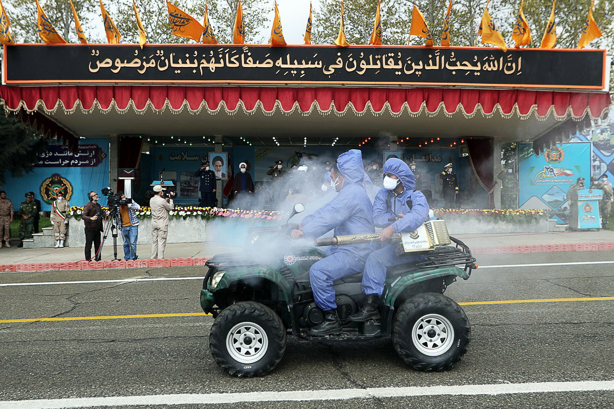 Dos militares desinfectan las calles de Teherán desde una moto.