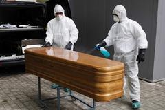 Trabajadores de una funeraria desinfectan un féretro en un hospital de Navarra.