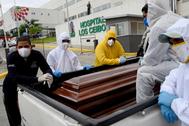 Personal de funeraria carga ataúdes junto a un hospital de Guayaquil.