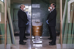Empleados de una funeraria junto a un ataúd en un crematorio de Burgos.
