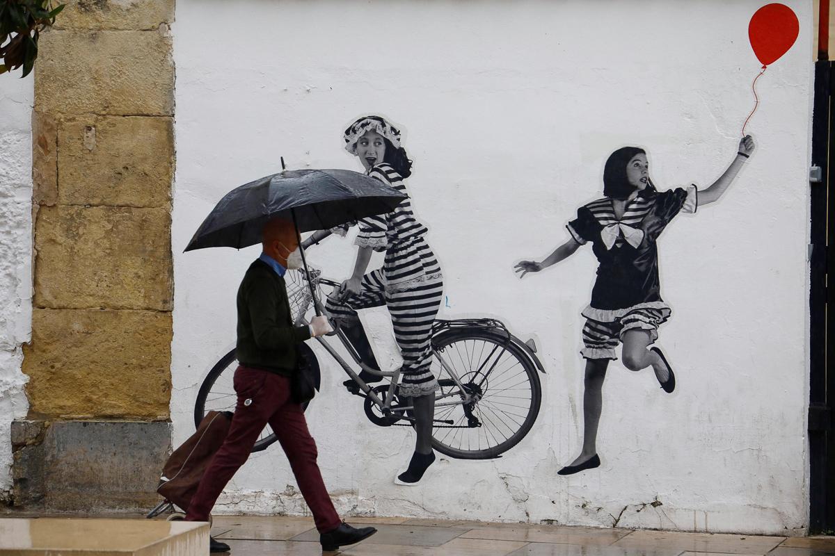 Una hombre pasa ante un grafiti en una calle de Córdoba.