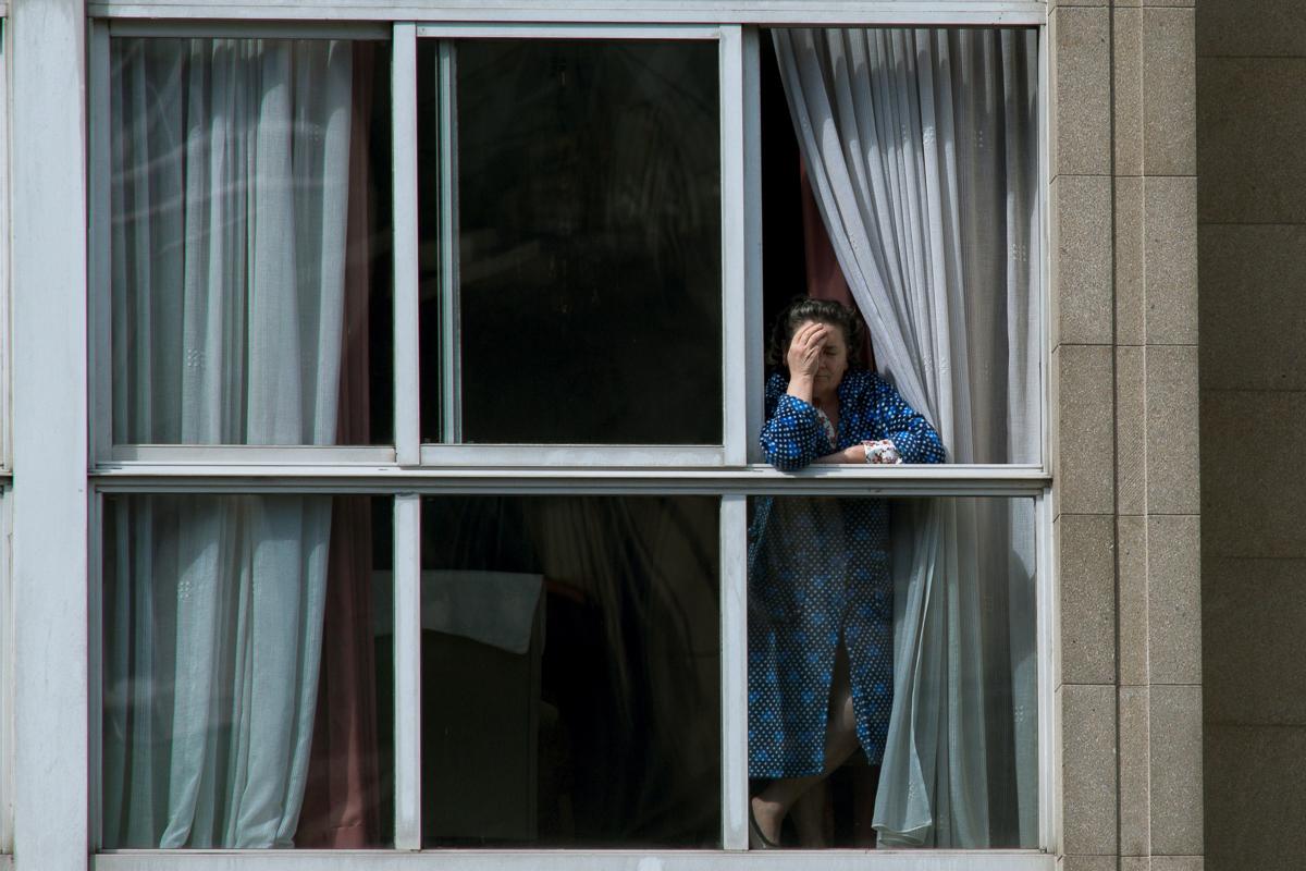 Una mujer asomada en la ventana de su vivienda, en Orense.