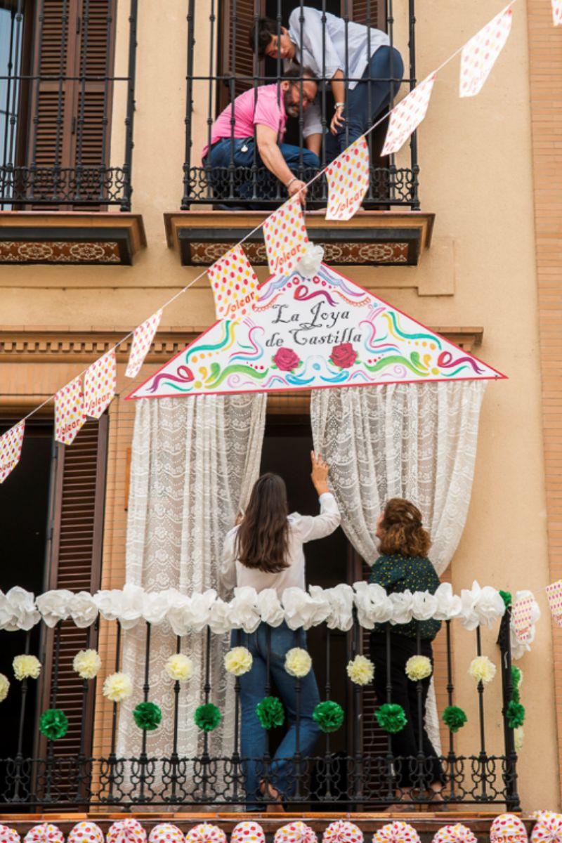 Vecinos de la calle Castilla, del barrio sevillano de Triana, decoran sus balcones para celebrar a su manera la Feria de Abril.