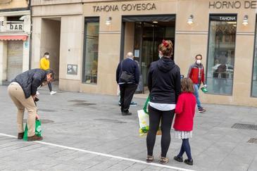 Una menor acompañada hace cola para comprar el pan en Zaragoza.
