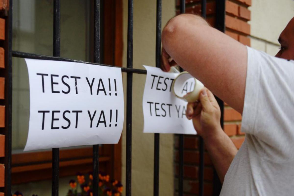 Un hombre coloca carteles en su vivienda de Valladolid reclamando la realización de test.