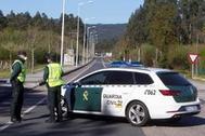 Un coche y dos agentes de la Guardia Civil.