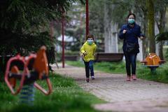 Una madre, corriendo con su hijo, ayer, en Valladolid.