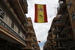 Banderas españolas con crespones negros colgadas en una calle de Sevilla.