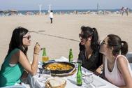Unas turistas se comen una paella en la playa de la Malvarrosa de Valencia