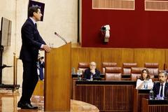 El presidente de la Junta, Juanma Moreno, se dirige a los parlamentarios ante la mirada de Susana Díaz y el consejero Juan Bravo.