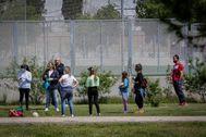 Varios niños con sus padres juegan en el Jardín del Turia de Valencia.