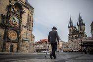Un hombre con mascarilla pasea por la Plaza de la Ciudad Vieja de Praga.