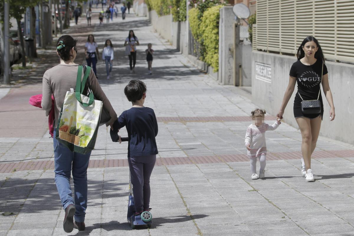 Niños pasean con sus madres, en Madrid.