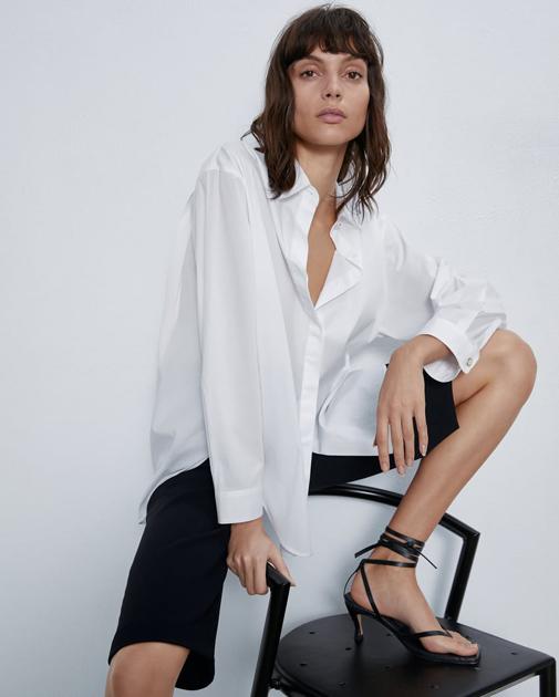 Camisa blanca con aberturas laterales en el bajo y botones ocultos. Es de Zara y cuesta solo 15,99 euros.