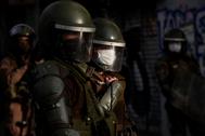 Policías vigilan a los manifestantes este lunes durante las protestas en la céntrica Plaza Italia, en Santiago