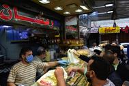 Sirios compran pasteles en un mercado de Damasco.
