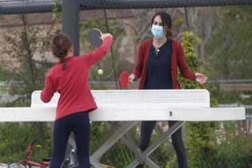 Una mujer y su hija juegan en un parque de Barcelona.