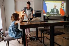 Una familia rusa confinada escucha un discurso de Putin en la televisión.