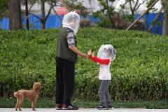 Un padre y su hijo, protegidos con bolsas en la cara, juegan en Pekín.