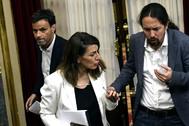 El líder de Podemos, Pablo Iglesias (dcha.), habla con la ministra de Trabajo, Yolanda Díaz, en presencia del diputado Jaume Asens, antes de la crisis del coronavirus.