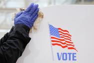 Un voluntario desinfecta un cartel electoral en Baltimore.