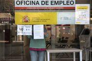 Un trabajador coloca unos carteles de aviso en una oficina de empleo de la Comunidad de Madrid.
