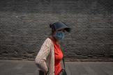 Una mujer con mascarilla pasea por una zona turística de Pekín.