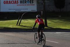 GRAF008. SALAMANCA.- Un lt;HIT gt;ciclista lt;/HIT gt; circula en Salamanca por delante de una valla publicitaria en la que se lee un mensaje de agradecimiento por la crisis del coronavirus.
