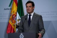 El presidente de la Junta, Juanma Moreno, en el atril con el nuevo logo del Gobierno andaluz.