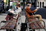 Un hombre y una mujer con mascarilla leen la prensa sentados en sendos bancos en Barcelona.