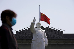 Un hombre con mascarilla frente a la estatua de Mao Zedong en Wuhan.