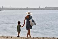 Una mujer y un niño pasean por la playa de El Zapillo de Almería.